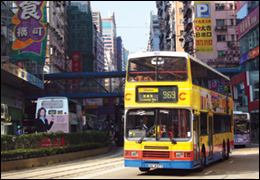 Double-decker bus driving in city (stock image)